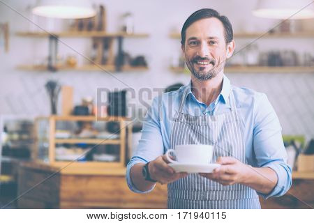 Waiting for guests. Positive senior smiling waiter holding cup of coffee and welcoming guests while working in the cafe