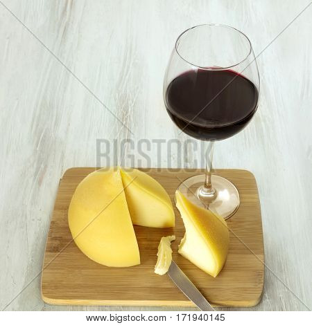 A photo of tetilla, a traditional Spanish soft cow milk cheese, with a slice cut off, and a glass of red wine, on a wooden board with a place for text