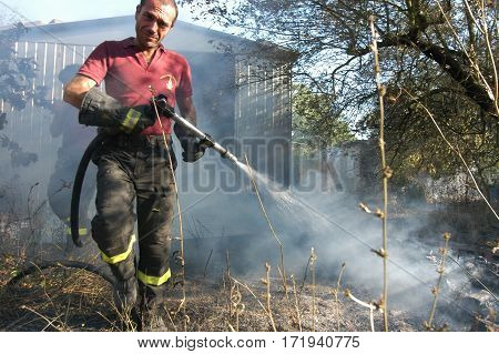 Bracciano Italy - July 14 2005: Severe Fires destroy forest in Italy. Italian firefighters work surrounded by the smoke to extinguish the fire July 14 2005 in Bracciano Lazio Italy.