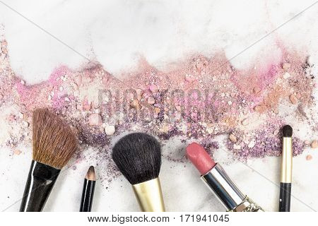 Makeup brushes, lipstick and pencil on a white background, with traces of powder and blush on it. A horizontal template for a makeup artist's business card or flyer design, with copy space