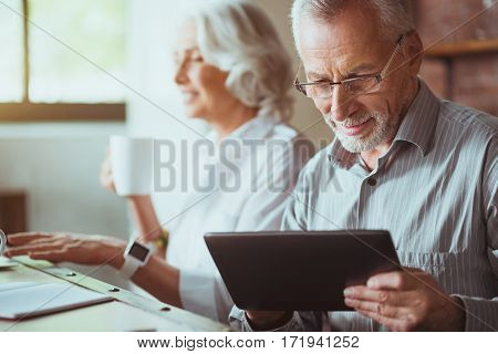 Moder aging generation. Pleasant smiling aged man using tablet while his wife sitting in the background and drinking coffee