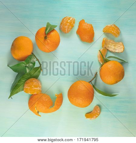 A square photo of vibrant orange tangerines with green leaves, slices and peels, shot from above on a teal background texture, forming a frame for copy space