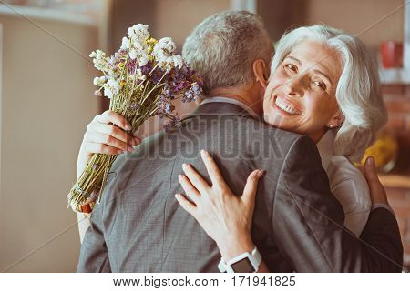 Eternal love. Pleasant cheerful loving aged couple standing in the kitchen and embracing while expressing their feelings
