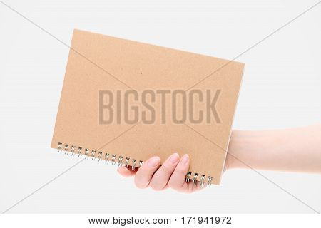 Hand holding blank notebook on white background