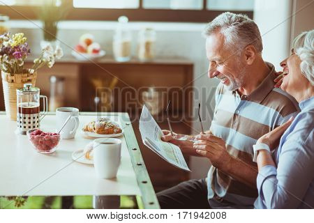 So funny. Cheerful loving aged couple sitting in the kitchen and reading newspaper while enjoying their breakfast