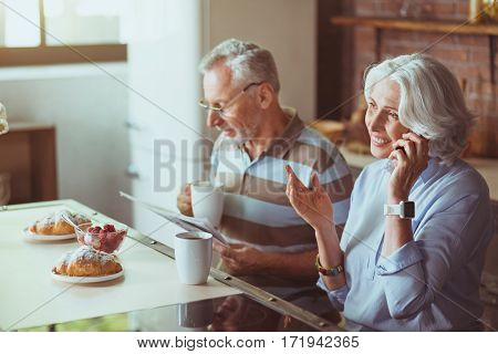 Good start of the day. Cheerful delighted aged woman talking on smart phone while her husband reading newspaper and drinking tea