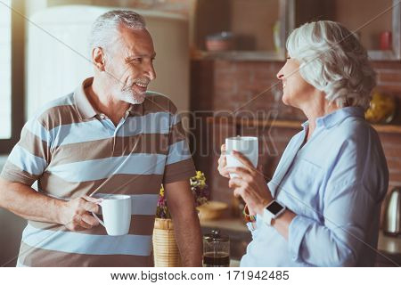Nice time together. Cheerful aged smiling couple drinking tea and talking while standing in the kitchen