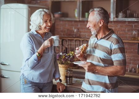 In a good mood. Cheerful loving aged couple having breakfast and expressing joy while standing in the kitchen