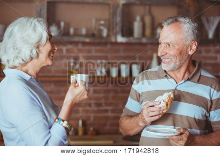 Warm atmosphere. Cheerful loving aged couple standing in the kitchen and talking while enjoying their breakfast