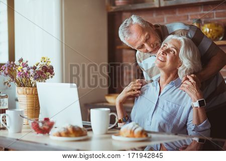 My dear. Pleasant delighted agd couple sititing in the kitchen and embracing while resting at home