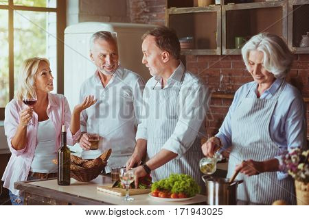 Longlasting friendship. Positive smiling aged couples standing in the kitchen and cooking while getting ready for festive dinner