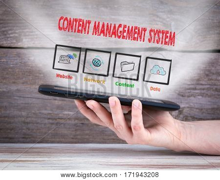 Content Management System concept. Tablet computer in the hand. Old wooden background.