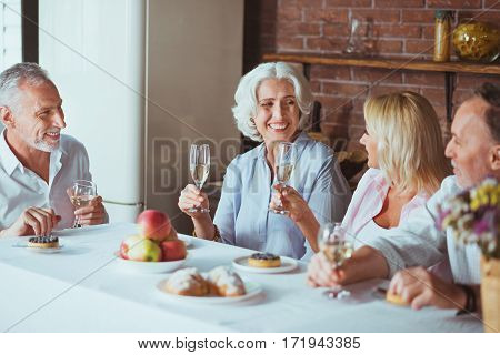 Nice celebration. Cheerful delighted smiling family sitting at the table and expressing joy while having festive meal