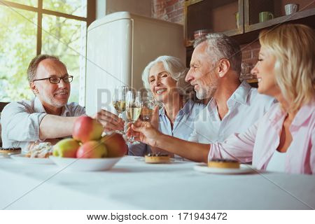 Our congratulations. Positive aged smiling friends sitting at the table and drinking sparkling wine while enjoying celebration