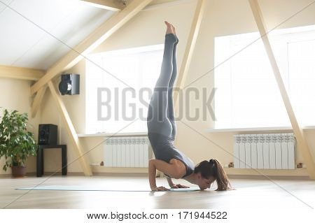 Young attractive sporty woman practicing yoga, standing in Ganda Bherundasana exercise, Formidable Face pose, working out, wearing grey sportswear, indoor full length, beautiful home interior