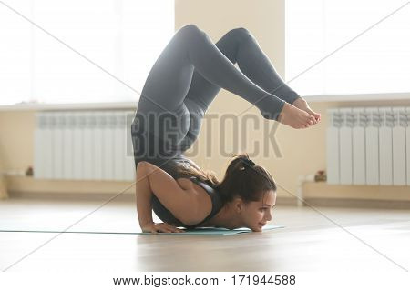 Young healthy attractive woman practicing yoga, standing in Ganda Bherundasana exercise, Formidable Face pose, working out, wearing grey sportswear, full length, beautiful home interior