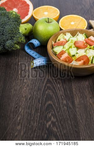Food For Diet And Measuring Tape On A Dark Wooden Table.