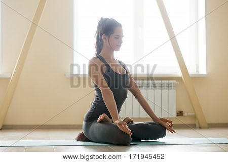 Young beautiful lady practicing yoga, sitting on meditation session at loft attic in the evening, meditating in Padmasana, Lotus pose, doing breathing exercises, using yogic pillow props. Full length