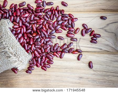 Dried red beans on a sack on wooden table