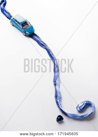Toy car on blue yarn road with question mark symbol. White background. Where to go travel destination future choice