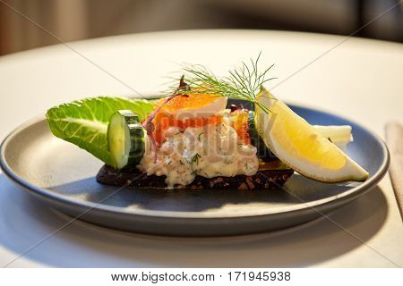 food, new nordic cuisine and cooking concept - close up of toast skagen with shrimps, lemon mayonnaise, caviar and buttery bread on plate at restaurant