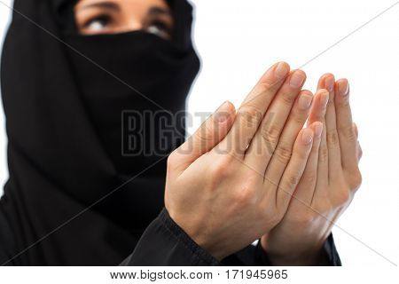 religion, faith, islam and people concept - close up of praying muslim woman in hijab over white background