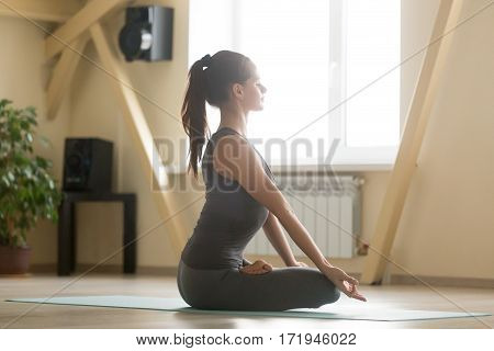 Young woman practicing yoga, sitting in Padmasana exercise, Lotus pose, meditation session with closed eyes, working out wearing grey sportswear, home interior indoor background, full length side view