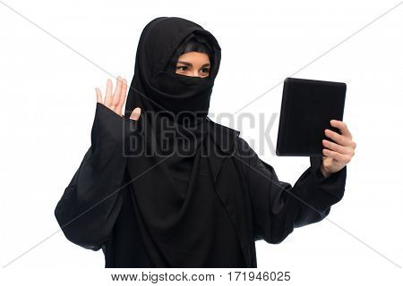 technology, communication and people concept - muslim woman in hijab with tablet pc computer havin video chat over white background
