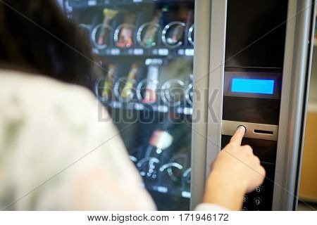 sell, technology and consumption concept - woman pushing button on vending machine operation panel
