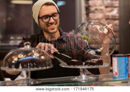 small business, food, people and service concept - happy man or barman with cakes and tongs at cafe counter