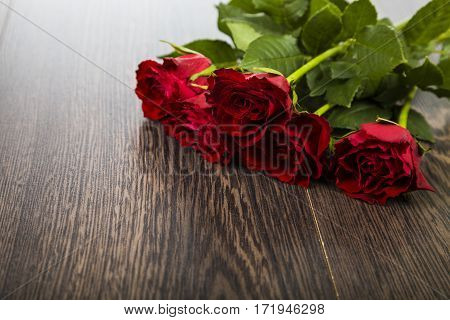 Red roses on a dark wooden background. Greeting card with Valentine's Day Birthday or Wedding.