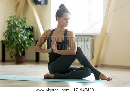Young attractive woman practicing yoga, sitting in Half lord of the fishes exercise, Ardha Matsyendrasana pose with namaste, working out, wearing sportswear, grey tank top, pants, indoor full length
