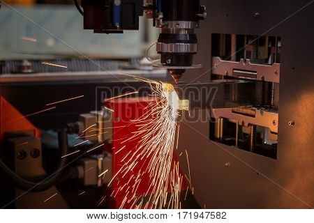 Cutting of sheet metal. Sparks fly from laser by automatic cutting CNC PLC machine. fabricate work factory production