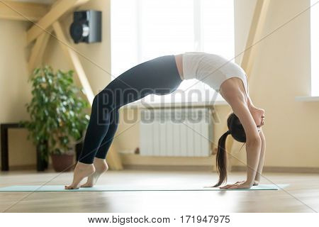 Young attractive woman practicing yoga, stretching in Urdhva Dhanurasana, Bridge pose, working out, wearing sportswear, white tank top, black pants, indoor full length, home or sport club interior