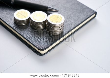 Business concept. Closeup stack of coins pen and notepad on white background.