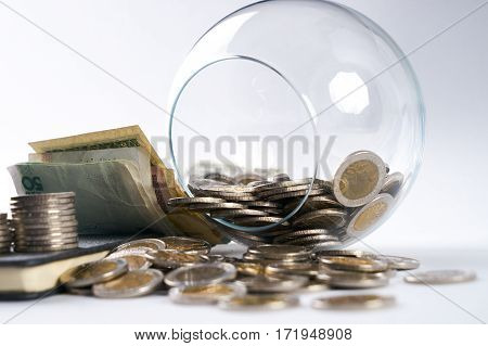Business concept. Stack of coins pen banknotes notebook and glass piggy box isolated on white.