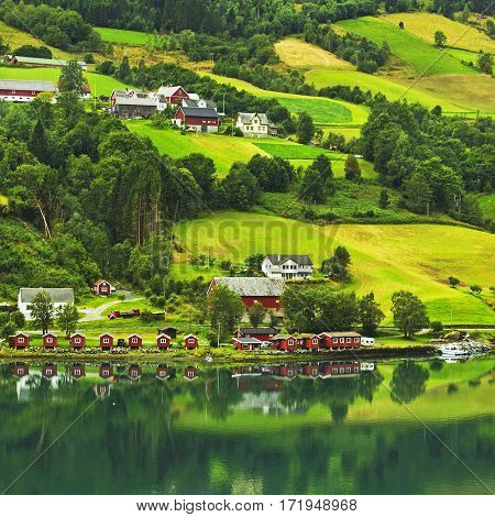 Norwegian village, green forested mountains landscape, Norway.