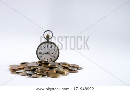 Old pocket watch with open cover on scattered coins isolated on white with copy space.Time is money concept.