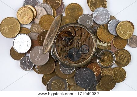 Clockwork with open cover on scattered coins.Top view.Time is money concept.