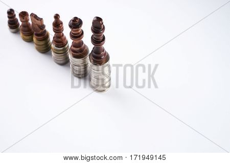 Growing coins stacks on white background. Black chess figures standing on coins meaning power and career growth. Financial growth saving money business finance wealth and success concept.