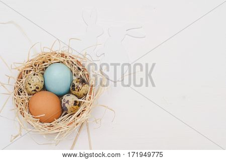 Hen and quail eggs in a handmade nest on white wooden background, Easter symbols