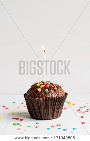 Birthday chocolate muffin with a small burning candle on white background