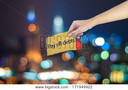 Hand Holding A Pay Off Debts Sign Made On Sugar Paper With City Light Bokeh As Background
