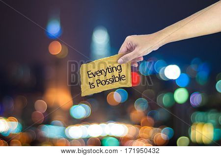 Hand Holding A Everyting Is Possible Sign Made On Sugar Paper With City Light Bokeh As Background