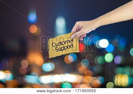 Hand Holding A Customer Support Sign Made On Sugar Paper With City Light Bokeh As Background