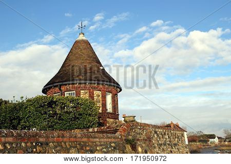 Round brick built tower with weather vane against blue cloudy sky in evening sunshine