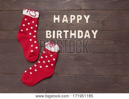 Happy Birthday And Socks Are On Wooden Background