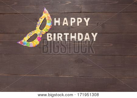 Happy Birthday And Mask Are On Wooden Background