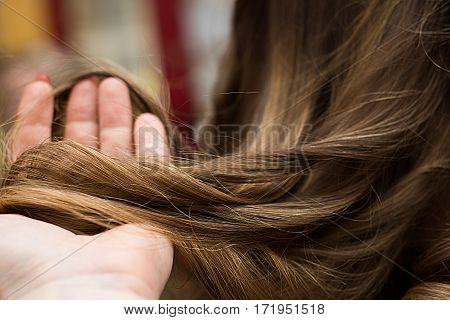 Close up view of hairdresser hand holding strand of hair preparing to cutting and dyeing hair.