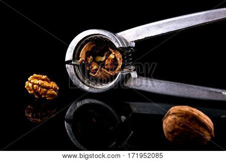 Delicious nuts and nutcrackers on a black background with reflection